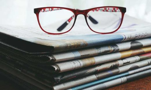 glasses on stack of newspapers